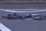 A flattened bike lies on a road with police tape