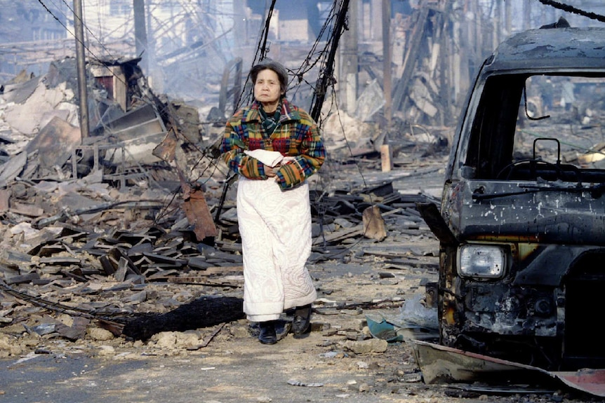 An older woman walks through a destroyed street in Kobe.