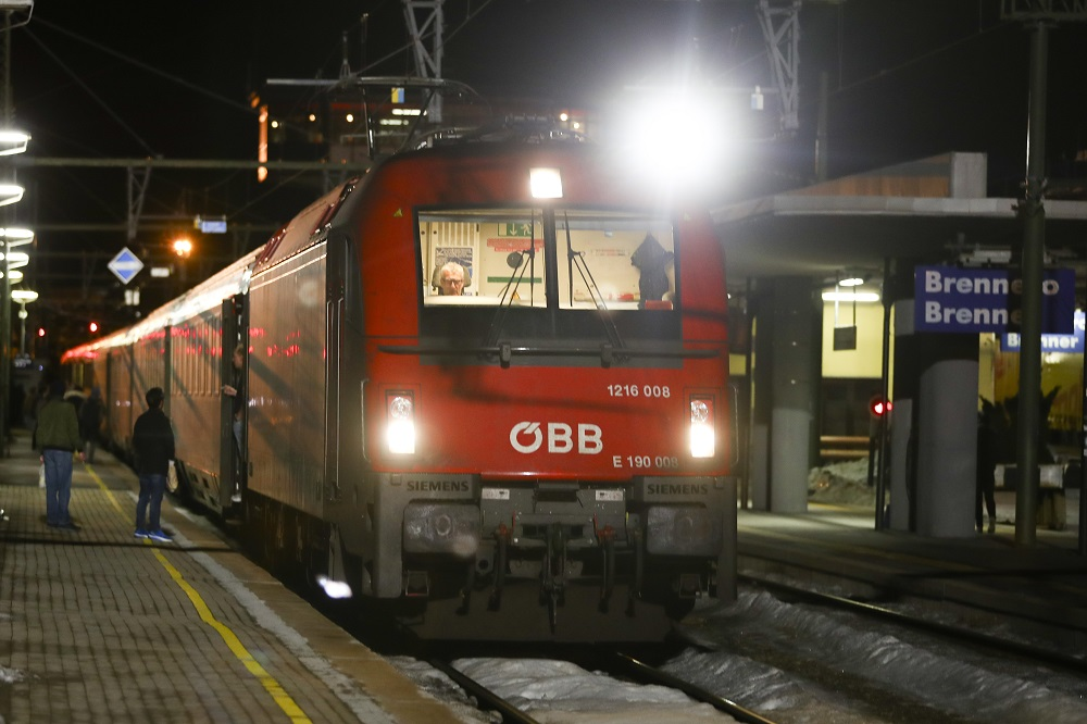A red train stops at a platform at the Brenner Pass in Italy.