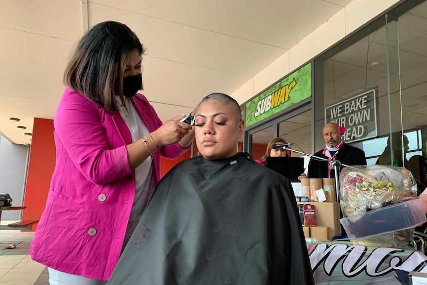 A woman wearing a face mask shaves the head of a girl.