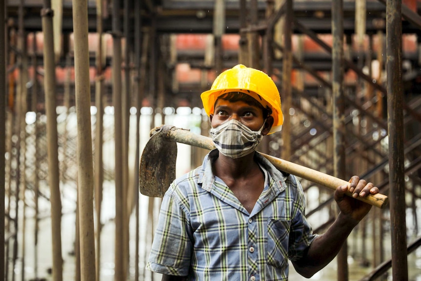 A young man in a hard hat and face mask