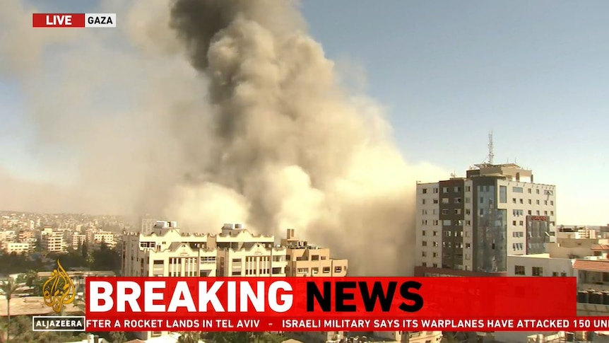 In this screenshot from an Al Jazeera feed, smoke rises after the al-Jalaa building in Gaza was levelled by Israeli forces.