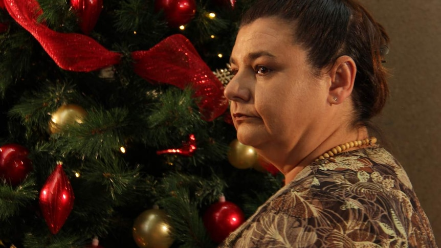 woman looking pensive in front of Christmas tree