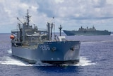 An Australian warship in the open ocean with another one behind it.