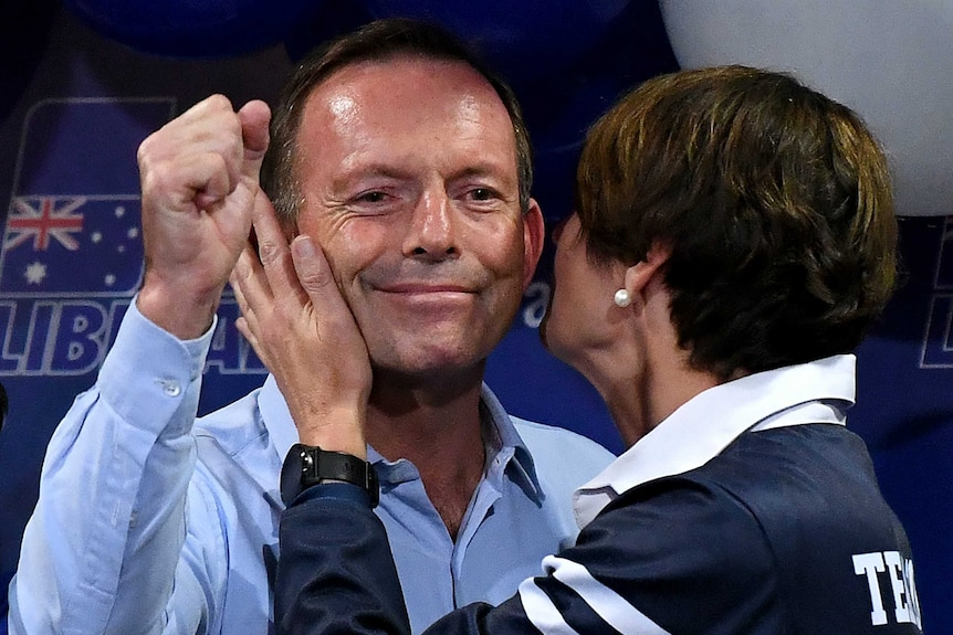 Tony Abbott with his fist in the air, with his wife Margie by his side