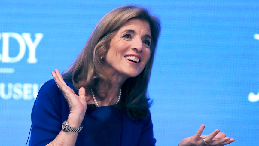 Caroline Kennedy smiling and gesturing against a blue background.