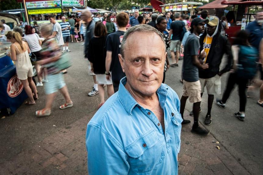 A man stands among a crowd.