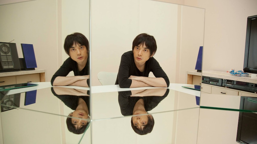 Japanese musician Cornelius looking at his reflection in a series of mirrors