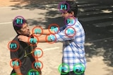 A drone image shows two men in a fighting position, with coloured circles around the points of contact.