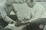 Two men kneel in a paddock, one holds a feral rabbit still while the other gives it an injection.