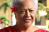 Fiame Naomi Mata'afa, with short grey hair, wearing a red dress, with a red flower in her hair.