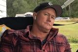 A man wearing a check shirt looks at the camera
