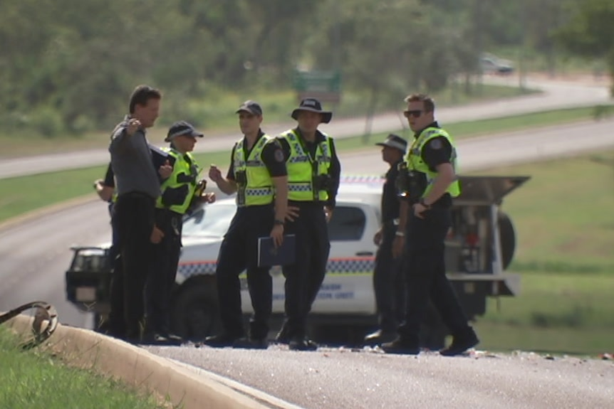 Police inspect the damage of a four-car crash on Tiger Brennan Drive with debris scattered across the road.