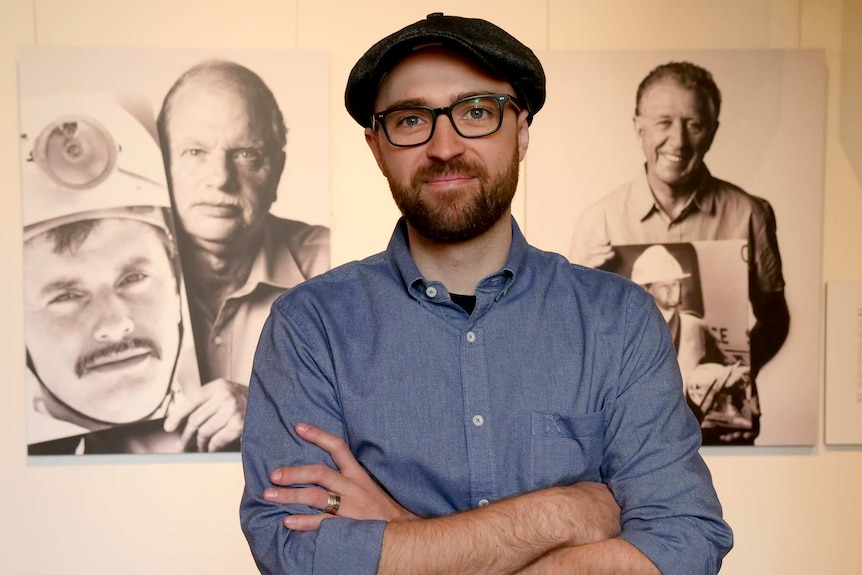 A man stands in front of a two large format photographs of people framed and hung on a wall.