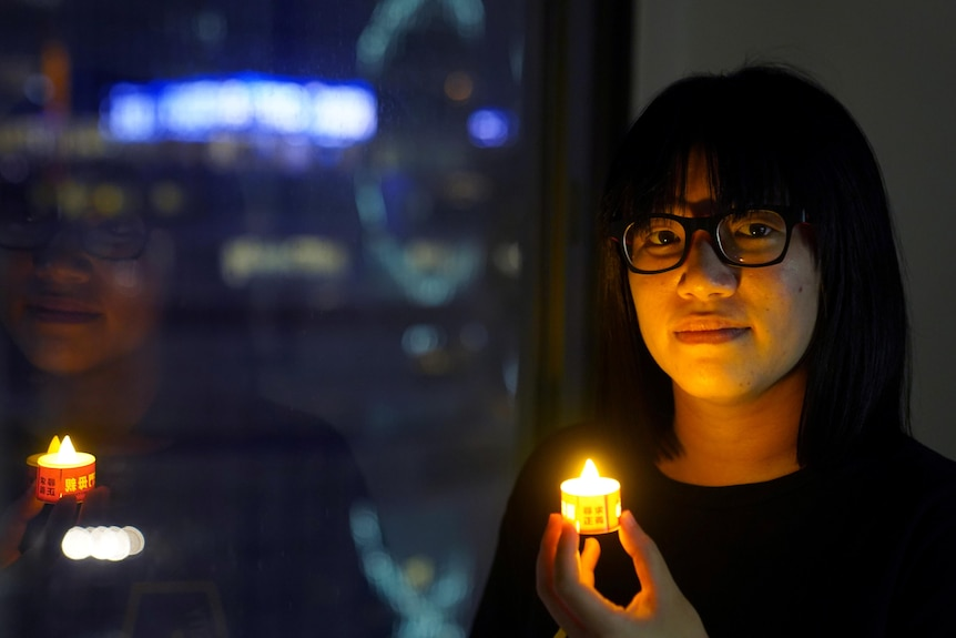 A woman whose face is illuminated by the tea light candle she's holding.