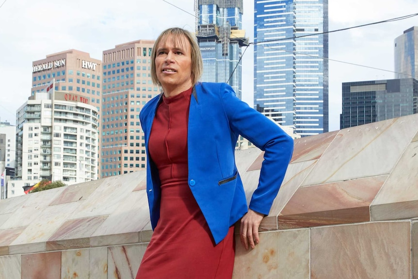 Transgender activist Melissa Griffiths wearing office attire and standing against sandstone wall with city in background.