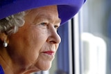 Britain's Queen Elizabeth II looks out from a window at the underwater stage at the Pinewood Studios