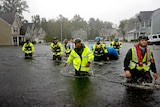 A group of men in high-vis work wear wade through a flooded street with one pulling along a blue inflatable raft