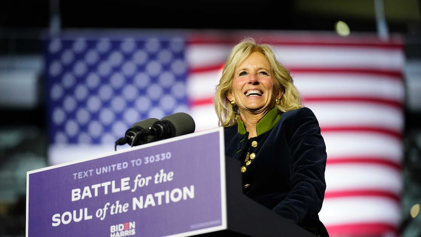 A woman with blond hair and wearing a long black coat stands in front of the US flag at a podium.
