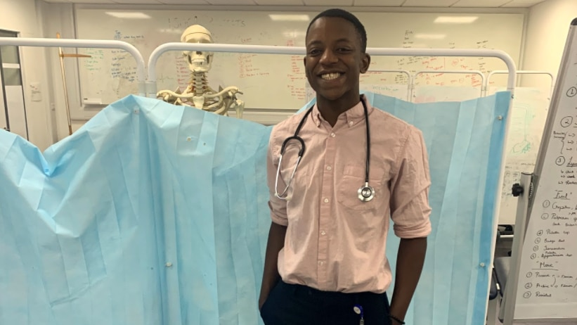 A dark-skinned young man standing in a medical teaching room with skeleton behind him. He is smiling and wearing a stethoscope.