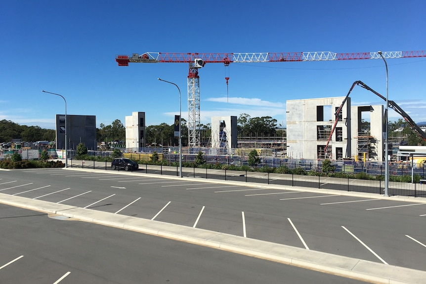 A crane on a construction site with a carpark in the foreground on a blue-sky day.