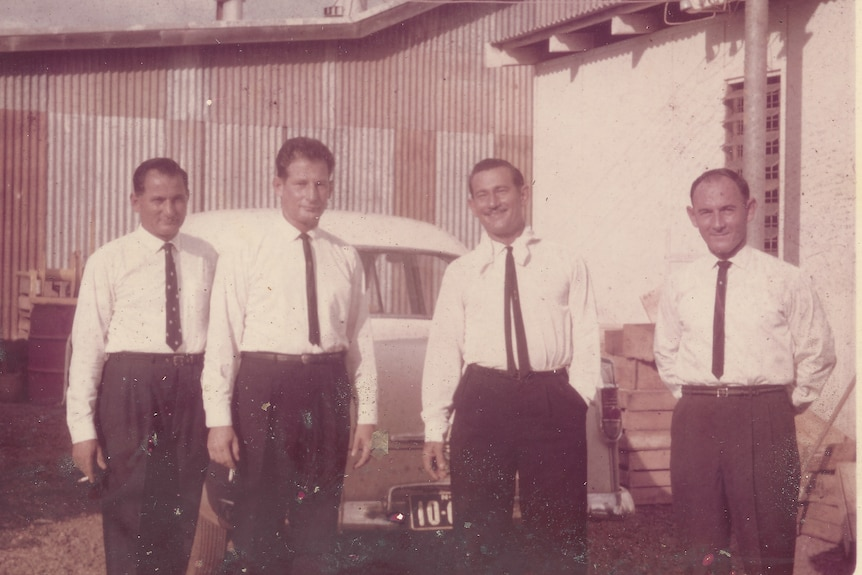 Four well-dressed men outside a corrugated iron building with a 1950s car behind. Two have cigarettes in their hands.