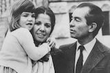 Black and white photo of a young girl in her mother's arms, father looking on.
