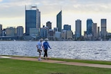 Two woman walking on South Perth foreshore with the Perth city skyline in the background.