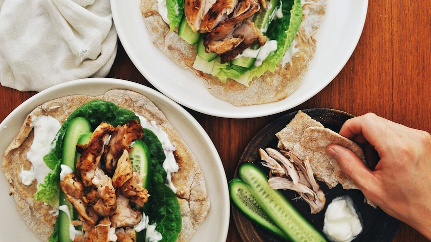 Two plates of grilled chicken served on flatbread with yoghurt sauce and vegetables, a satisfying family dinner recipe.