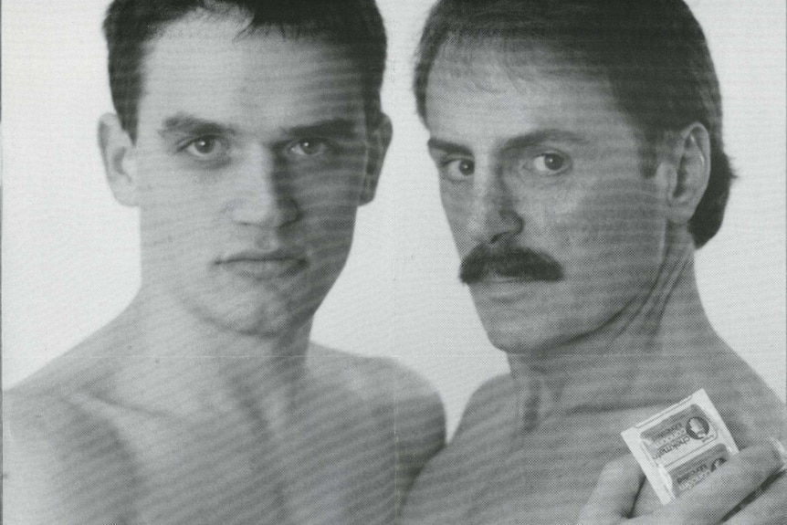 Two shirtless men embrace, one holding a condom in his hand, with the text: 'It's black and white ...condomwise.'