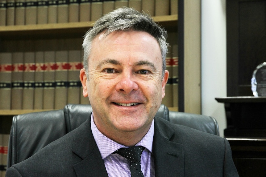 A man in a suit smiles at the camera