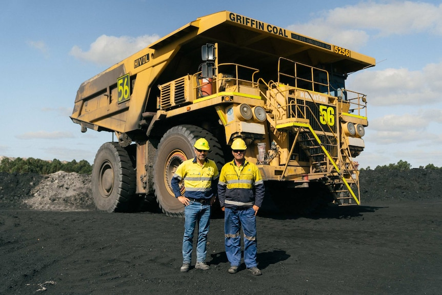 Two men stand in front of a haul truck at Griffin Coal Mine in Collie, WA.