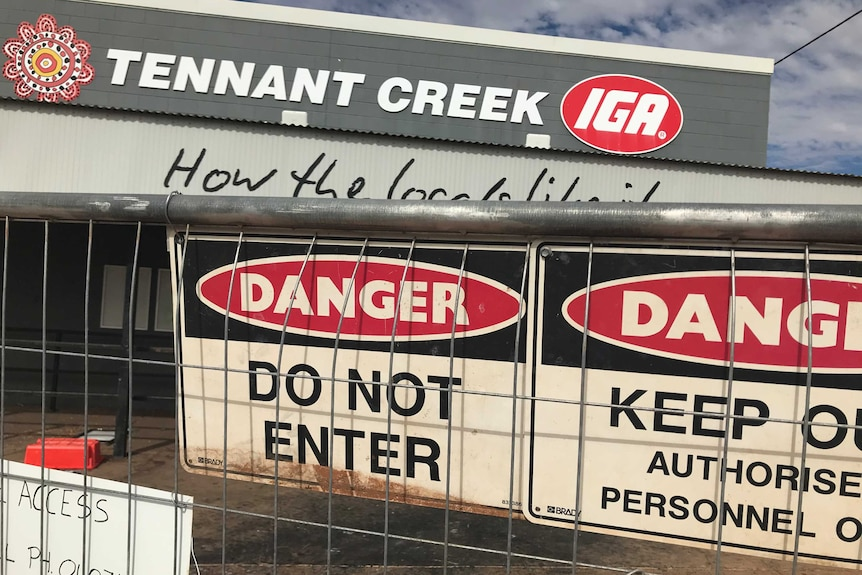 Danger do not enter signs on a fence, which is in front of a building. A sign on the building says Tennant Creek IGA.