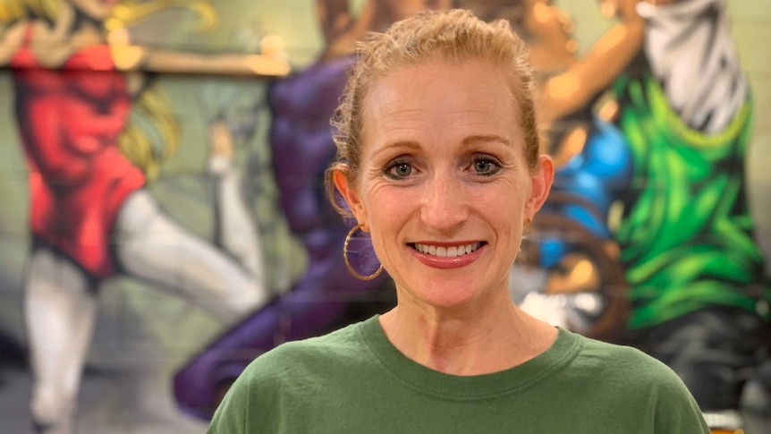 Ms Parnell smiles in front of a mural of people dancing.
