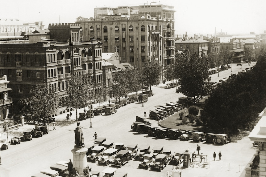 A black and white photo of buildings, parked cars and people looking west down North Terrace