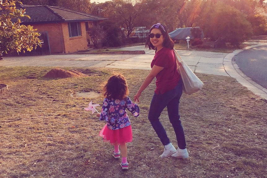 Carla Gee holding hands with her daughter, who has her back to the camera, outside a suburban brick house