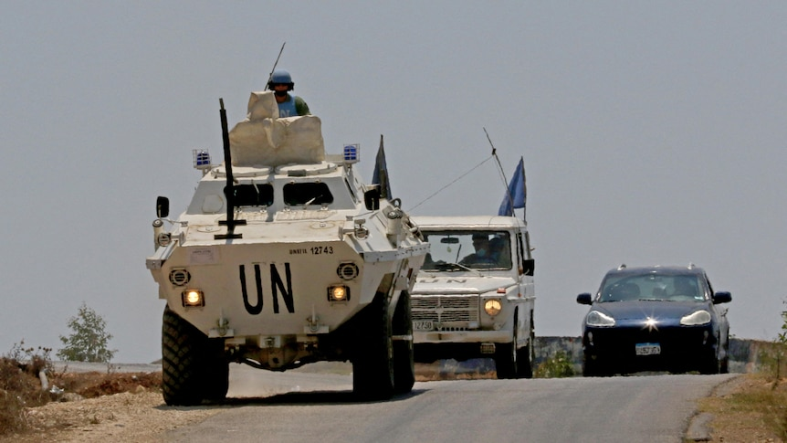 Two UNIFIL vehicles are seen driving on a road near Lebanon's border with Israel.