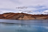 A pristine blue lake with bare, jagged hills behind on a cloudy day.