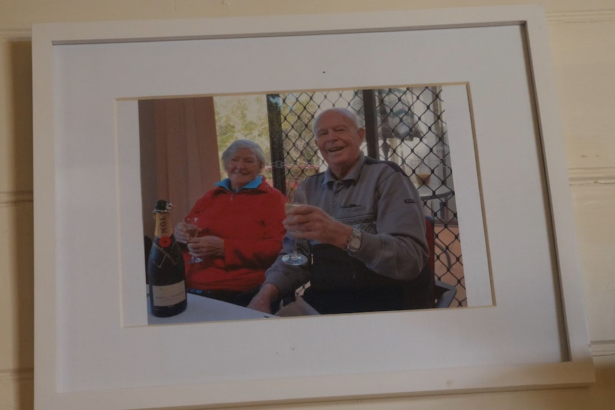 A photo of an old man and woman smiling in a photo.