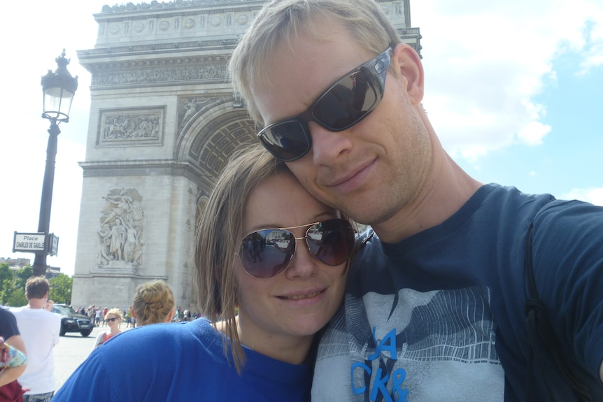 A husband and wife smile and stand in front of the large monument of the Arc de Triomphe in Paris.