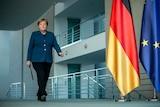 Angela Merkel walks in a navy blazer down a corridor with a large German and EU flag.