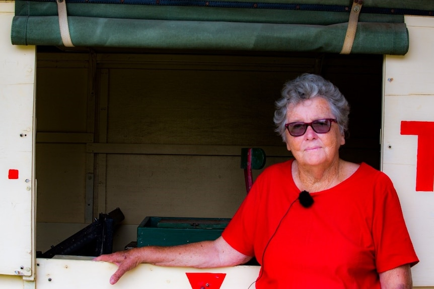 A woman wearing sunglasses and a red-tshirt, with short grey hair, stands with her arm resting on an empty windowsill.