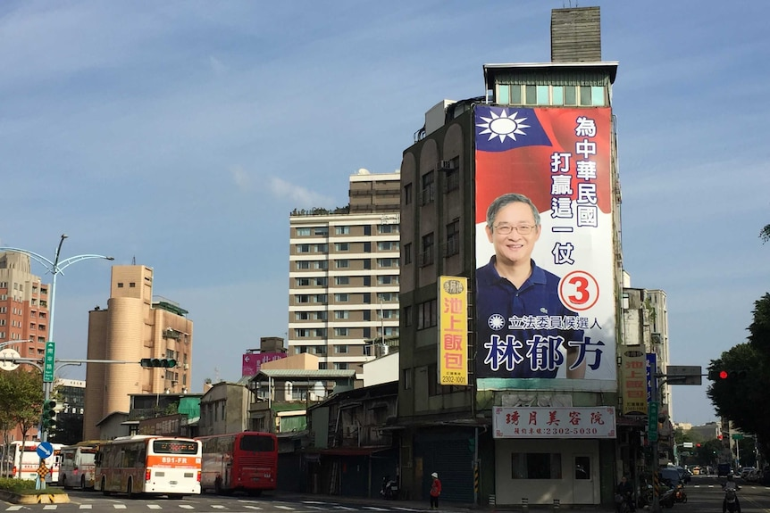 The side of a building is covered in a 'how to vote' election advertisement