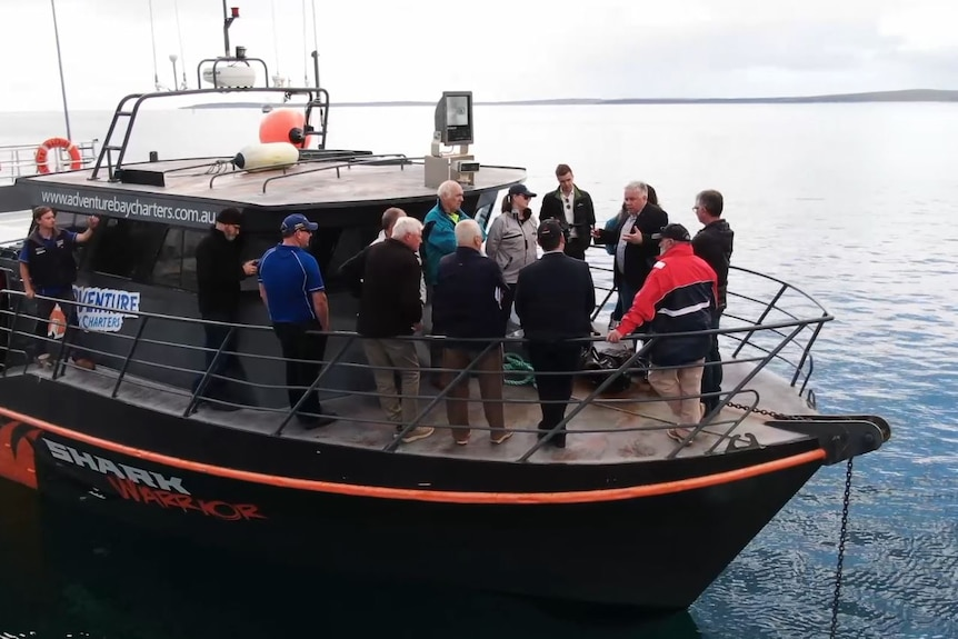 a group of people stand at the front of a boat talking