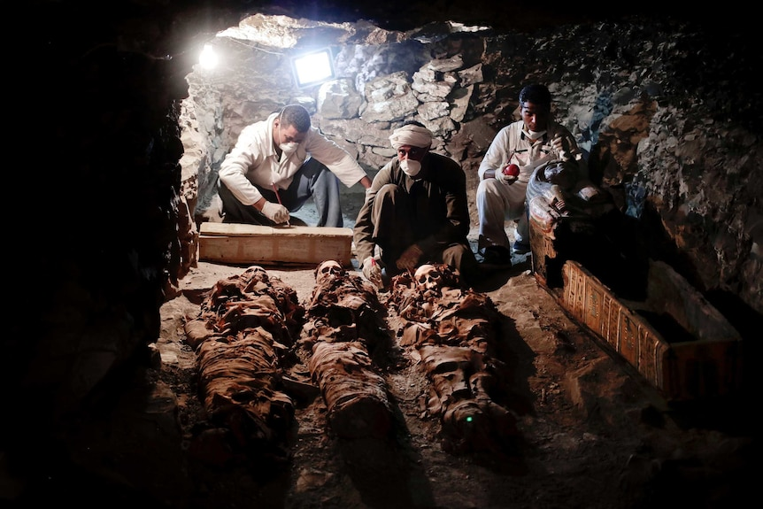 Archaeologists work on mummies inside a tomb