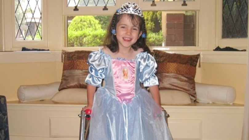 Hannah as a child dressed as a Disney princess, smiling at the camera.