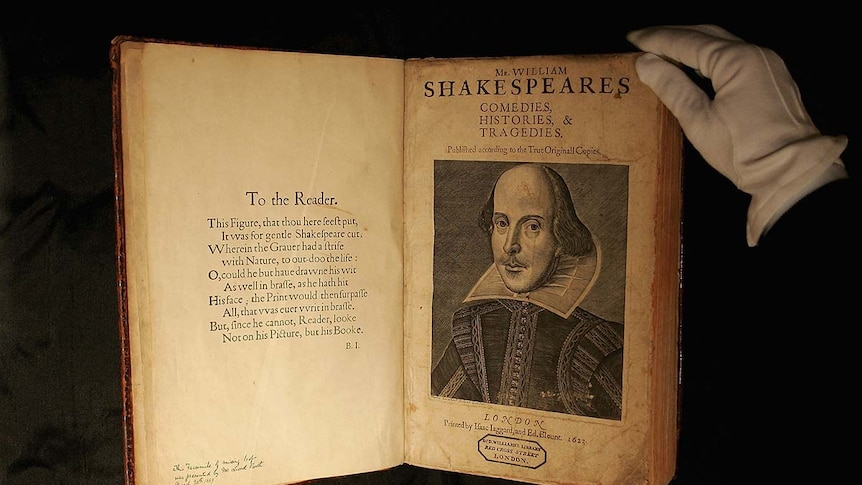 Person wearing gloves handles First Folio edition of Shakespeare's plays.