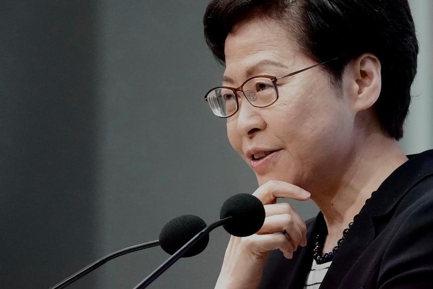 Hong Kong leader Carrie Lam smirks as she speaks into microphones
