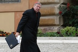 George Pell carries a briefcase as he arrives for a meeting