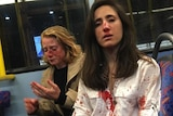 Two women sit on a bus seat with blood dripping down their faces